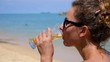 Woman Drinking Juice with Ice on Beach. Slow Motion.