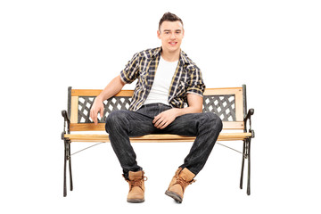 Cool young male model sitting on a bench