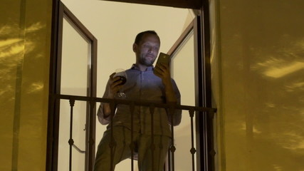 Young man sending sms on smartphone on balcony at night