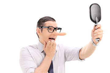 Scared man with long nose looking in a mirror