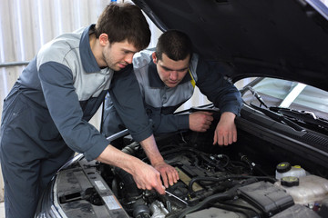 Two auto mechanics examining car with open hood