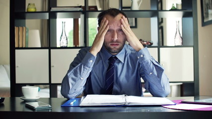 Tired businessman having headache, head pain in the office