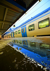 Commuter train reflecting in platform puddle