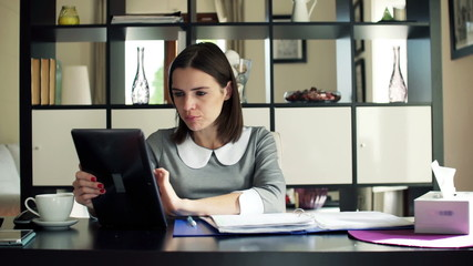 Businesswoman with documents during video chat on tablet compute