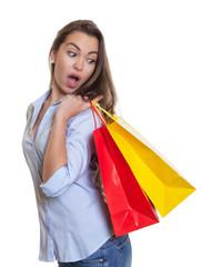Zufriedene Frau mit braunen Haaren und Einkaufstaschen