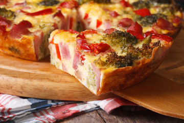 Piece of quiche with broccoli, pepper, bacon macro.