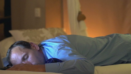 Young businessman sleeping after work on bed at home