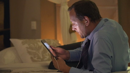 Businessman watching film on tablet computer and lying on bed at