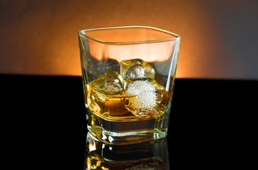 whiskey glass with ice and warm light on black background