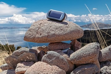 Gps device is placed on stacked rocks of geochache hide.