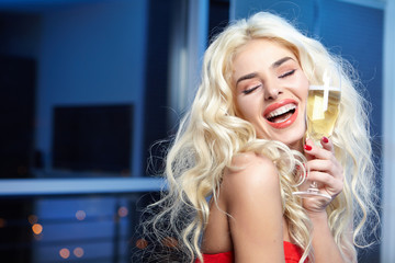 Happy and beautiful blond woman in a party red dress with a glas