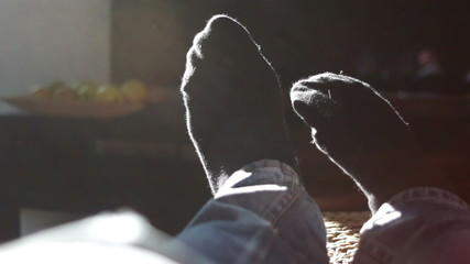 Male feet with socks in window light on couch