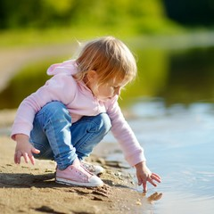 Adorable toddler girl playing by a river