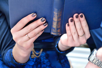 Woman holding a blue book with two hands with engagement ring on