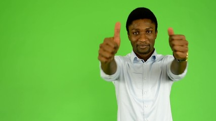 black man shows thumbs on agreement - green screen