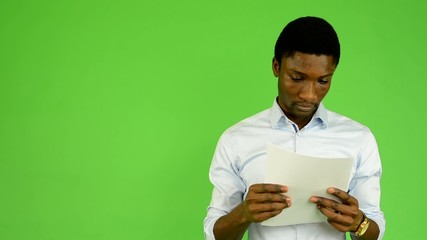 young handsome black man reads documents  - green screen