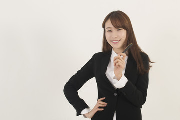 Attractive young asian businesswoman with a pen