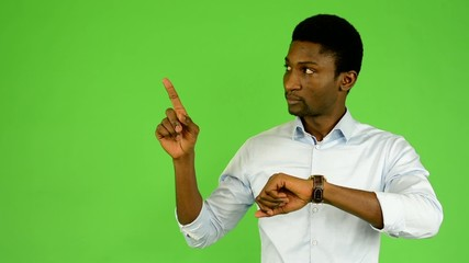 black man points to watch - green screen - studio