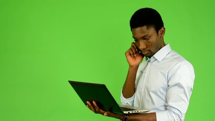 black man works on notebook and phone - green screen - studio