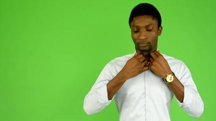 black man adjusts clothing, smiles - green screen