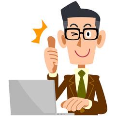 パソコンの前でサムズアップするメガネの男性