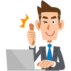 パソコンの前でサムズアップする若いビジネスマン