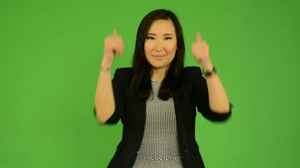 asian woman shows thumbs on agreement - green screen