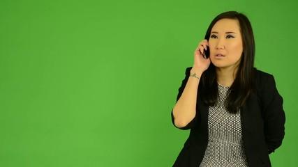 asian woman phone (serious face) - green screen