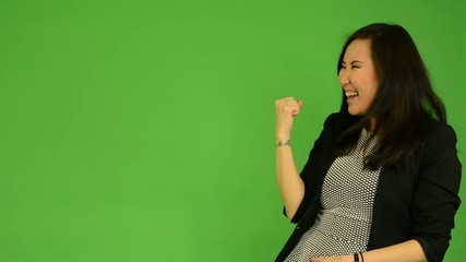 attractive asian woman rejoices - green screen