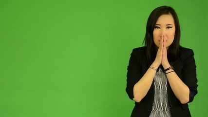 young attractive asian woman prays - green screen studio