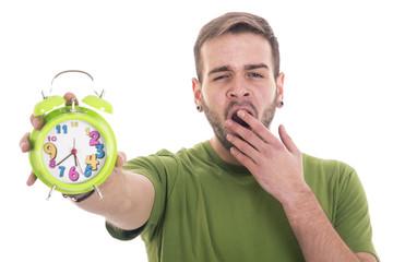 Yawning guy holding alarm