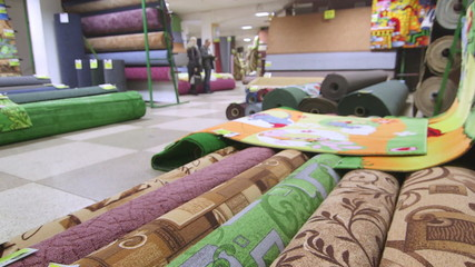 Rolls of carpets and rugs in store