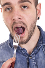 Handsome guy eating grapes into bowl with a fork
