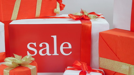 Wrapped red white gift boxes with word Sale closeup