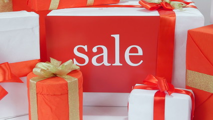 White red gift boxes with gold ribbons and word Sale