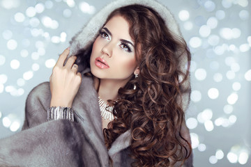 Beauty Fashion Model Girl in Mink Fur Coat and furry hood. Beaut