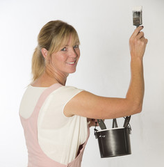 Woman wearing overalls holding paint brush