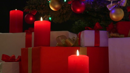 Burning candles and gifts boxes under Christmas tree