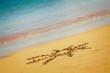 sun drawn on sandy beach