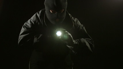 Thief stealing stacks of money at night