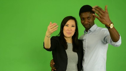 happy multicultural couple invite and smile - green screen