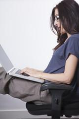 sitting woman typing on laptop