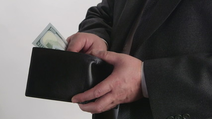 Business person takes out dollars from a leather wallet