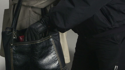 Pickpocket taking wallet from a womans handbag