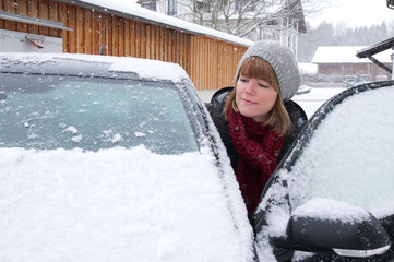 Junge Frau steigt in verschneites Auto