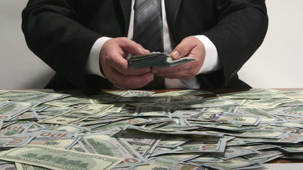 Business person counting lot of $100 american dollar bills