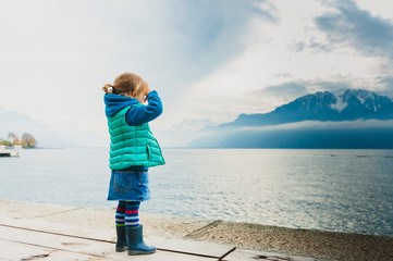 Adorable toddler girl playing by the lake