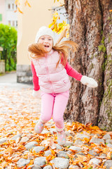 Adorable little girl having fun outdoors on a nice autumn day