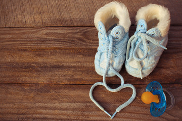 heart symbol is drawn laces of children's shoes and a pacifier