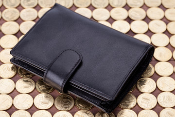 Black leather wallet on golden coins